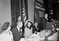 First lady Jacqueline Kennedy is all smiles as she attends a breakfast held by the Chamber of Commerce in Fort Worth, Texas, on Nov. 22, 1963. Seated at the dais, from left, are, Lady Bird Johnson, Vice President Lyndon B. Johnson, Mrs. Kennedy and President John F. Kennedy. The man at podium is unidentified. (Photo: Ferd Kaufman/AP)