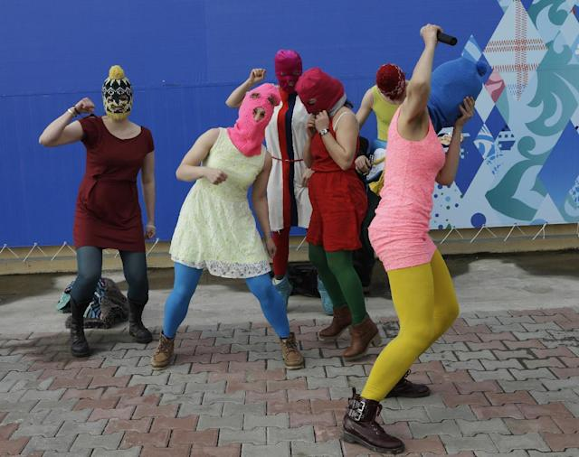 Members of the punk group Pussy Riot, including Nadezhda Tolokonnikova in the blue balaclava and Maria Alekhina in the pink balaclava, stage a protest performance in Sochi, Russia, about 30km (21miles) from where the Winter Olympics are being held, on Wednesday, Feb. 19, 2014. The group was attacked by about a dozen Cossack militiamen and other security officers almost immediately as they ran out of a nearby restaurant. (AP Photo/Morry Gash)