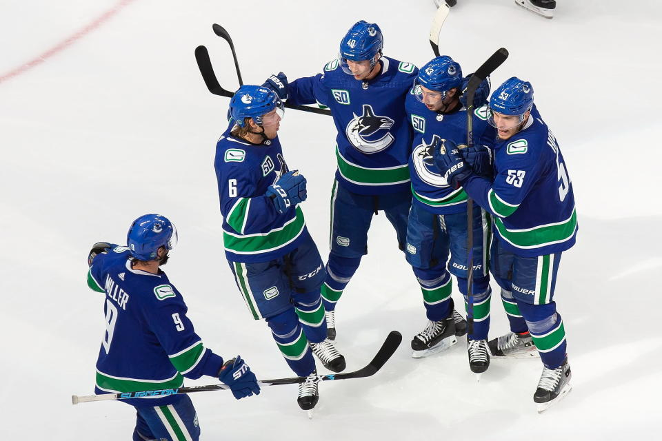 Vancouver Canucks' J.T. Miller (9), Brock Boeser (6), Elias Pettersson (40), Quinn Hughes (43) and Bo Horvat (53) celebrate a goal against the Minnesota Wild during the third period of an NHL hockey playoff game in Edmonton, Alberta, Tuesday, Aug. 4, 2020. (Codie McLachlan/The Canadian Press via AP)