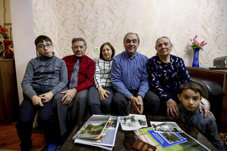 From left: Adil Sharifov's grandson Ramazan Sharifov, uncle Ramiz Humbatov, sister Kamala Sharifova, Adil Sharifov, his mother Adila Ahmadova and grandson Tariyel Sharifov pose for a photo at home in Baku, Azerbaijan, Friday, Nov. 20, 2020. Adil Sharifov, 62, who left his hometown in 1992 during the first war and lives in Azerbaijan's capital, Baku, knows he will find similar devastation if he returns to the city of Jabrayil, which he longs to do. (AP Photo/Aziz Karimov)