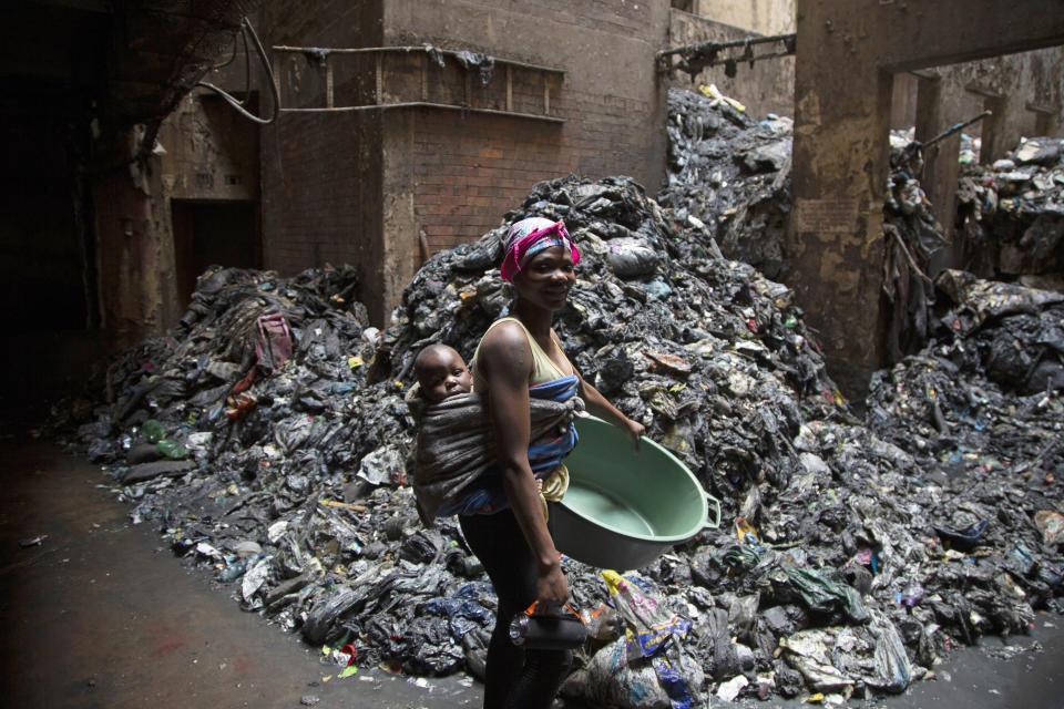A woman with her child on her back works on daily chores as she passes piles of rubbish in a derelict building where she lives in Hillbrow, Johannesburg, South Africa, Monday, March 29, 2021. The building, which houses an orphanage, is being renovated to create accommodation in the inner city. (AP Photo/Denis Farrell)