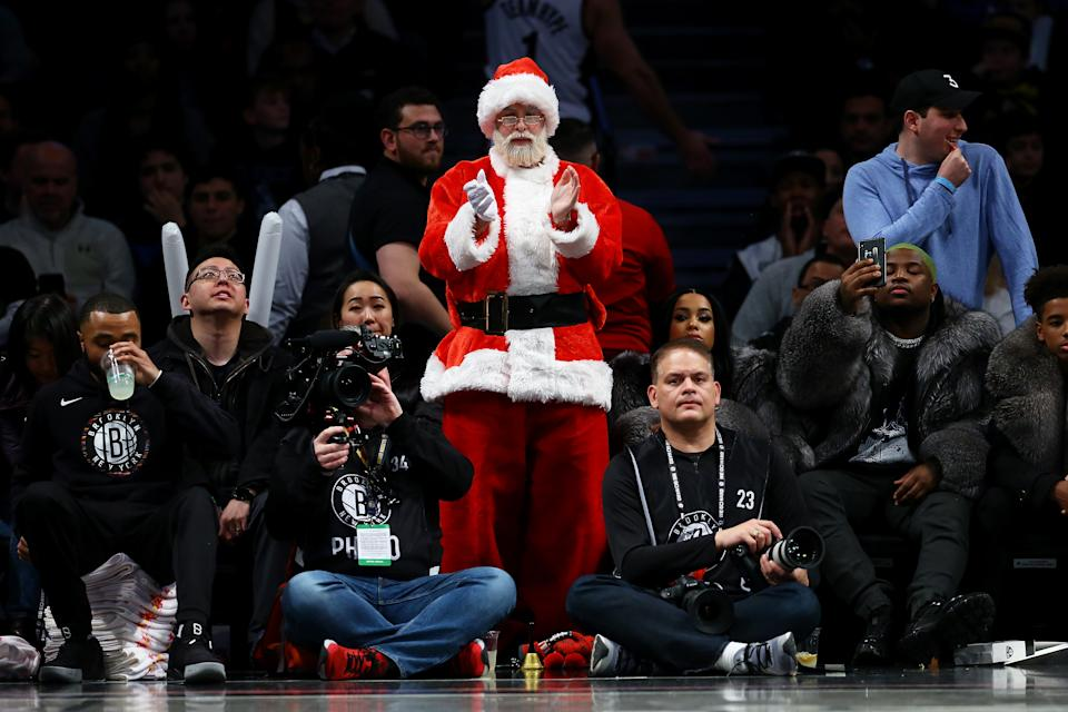 NEW YORK, NEW YORK - DECEMBER 08: A fan dressed as Santa Claus attends the game between the Brooklyn Nets and the Denver Nuggetsat Barclays Center on December 08, 2019 in New York City. Brooklyn Nets defeated the Denver Nuggets 105-102. NOTE TO USER: User expressly acknowledges and agrees that, by downloading and or using this photograph, User is consenting to the terms and conditions of the Getty Images License Agreement.  (Photo by Mike Stobe/Getty Images)