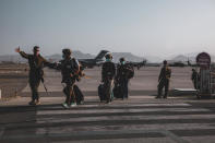 A Marine assigned to the 24th Marine Expeditionary Unit (MEU) escorts Department of State personnel to be processed for evacuation at Hamid Karzai International Airport, in Kabul, Afghanistan, Sunday, Aug. 15, 2021. (Sgt. Isaiah Campbell/U.S. Marine Corps via AP)