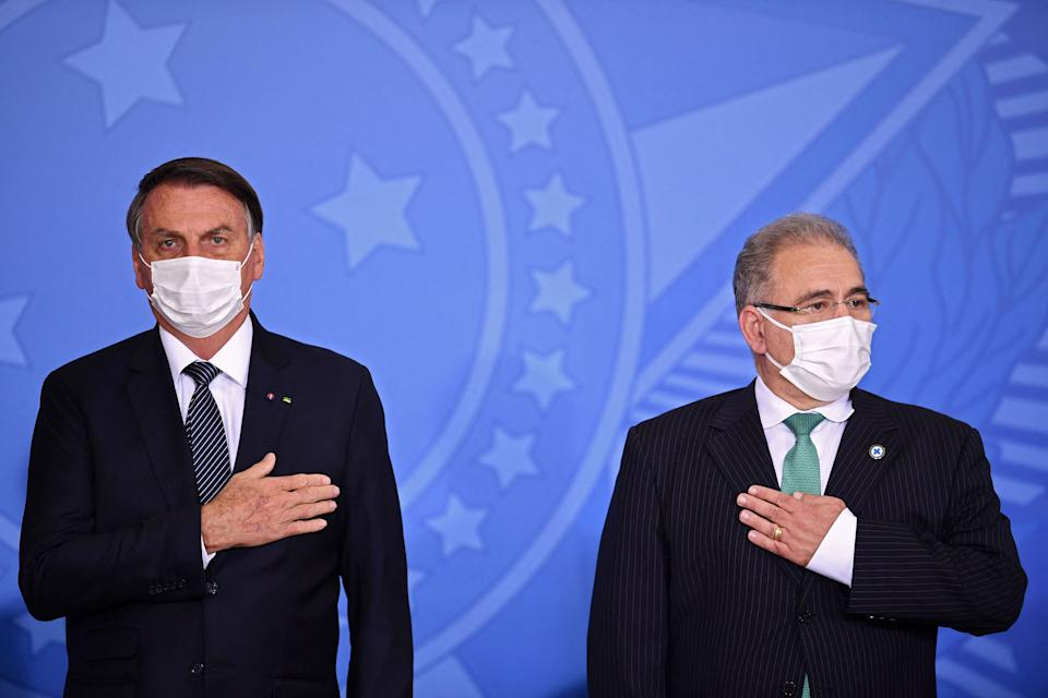 Brazilian President Jair Bolsonaro (L) and his Health Minister Marcelo Queiroga gesture during the announcement that the public healthcare system will cover expanded heel prick tests at Planalto Palace, in Brasilia, on May 26, 2021. (Photo by EVARISTO SA / AFP) (Photo by EVARISTO SA/AFP via Getty Images)