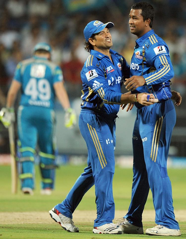 Mumbai Indians' cricketer Sachin Tendulkar (C) congratulates bowler Pragyan Ojha (R) after taking the wicket of Pune Warriors India's batsman Steve Smith (L)  during the IPL Twenty20 cricket match between Pune Warriors India and Mumbai Indians at The Subroto Roy Sahara Stadium in Pune on May 3, 2012.   AFP PHOTO / INDRANIL MUKHERJEE RESTRICTED TO EDITORIAL USE. MOBILE USE WITHIN NEWS PACKAGE            (Photo credit should read INDRANIL MUKHERJEE/AFP/GettyImages)