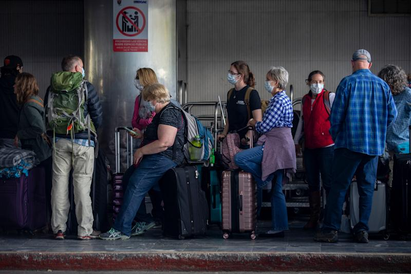 Travelers wait in line for a charter flight coordinated by the U.S. embassy at the La Aurora airport in Guatemala City, Monday, March 23, 2020. American citizens stranded abroad because of the coronavirus pandemic are seeking help in returning to the United States. (AP Photo/Moises Castillo)