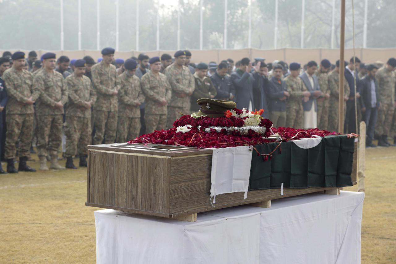 People offer a funeral prayers of a soldier in Lahore, Pakistan, Wednesday, Dec. 13, 2017. Pakistan's army says militants opened fire on an army vehicle on patrol in the country's mountainous northwestern region near the Afghan border, killing two soldiers. (AP Photo/K.M. Chaudary)