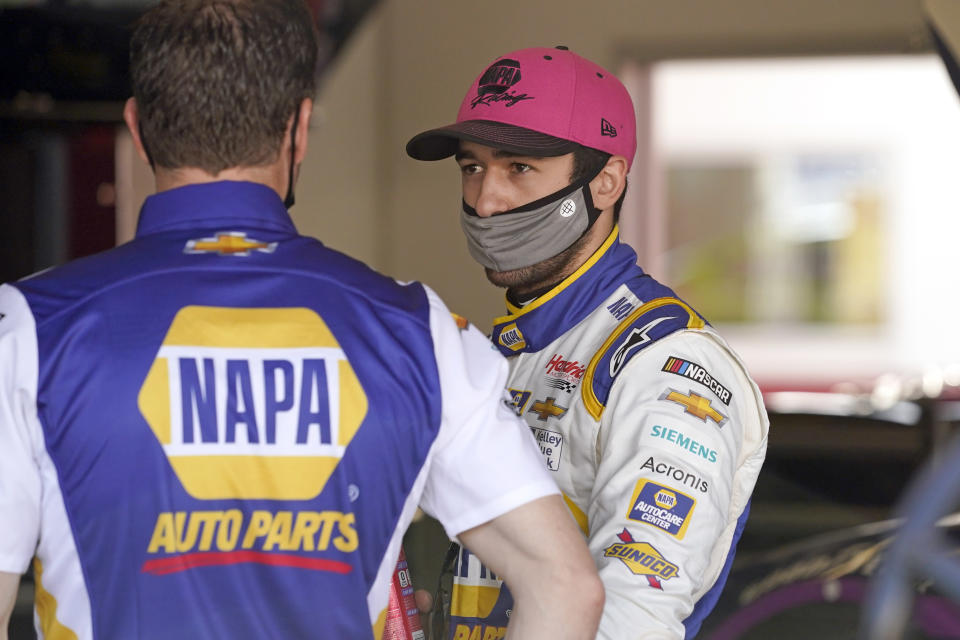 Chase Elliott, right, talks with a crew member in his garage during a NASCAR Daytona 500 auto race practice session at Daytona International Speedway, Wednesday, Feb. 10, 2021, in Daytona Beach, Fla. (AP Photo/John Raoux)
