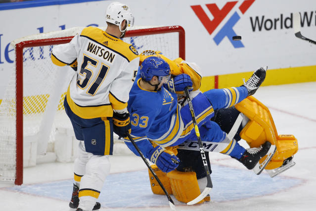 St. Louis Blues' Jordan Kyrou, front center, is tripped up by Nashville Predators goaltender Juuse Saros, back center, of Finland, as Austin Watson defends during the third period of an NHL hockey game Saturday, Feb. 15, 2020, in St. Louis. (AP Photo/Billy Hurst)