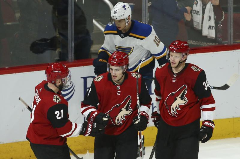Arizona Coyotes center Nick Schmaltz (8) celebrates his goal against the St. Louis Blues with Coyotes center Derek Stepan (21) and Coyotes center Carl Soderberg (34) as St. Louis Blues center Brayden Schenn (10) skates past during the third period of an NHL hockey game Tuesday, Dec. 31, 2019, in Glendale, Ariz. The Coyotes defeated the Blues 3-1. (AP Photo/Ross D. Franklin)