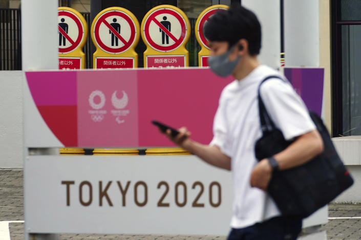 A man wearing a protective mask to help curb the spread of the coronavirus walks past a banner for the Tokyo 2020 Olympic and Paralympic Games on May 11, 2021, in Tokyo. The Japanese government was quick to respond on Tuesday, May 25, 2021 to U.S. travel warning for Americans against traveling to Japan and denied impact on Olympic participants, as the country determinedly prepare to host the postponed games in two months. (AP Photo/Eugene Hoshiko)