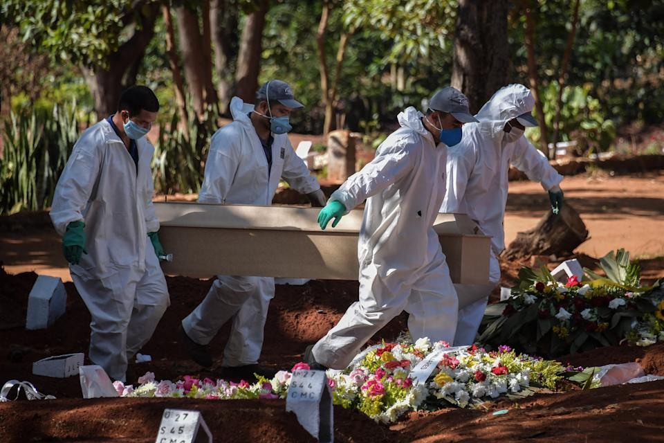 TOPSHOT - Employees carry the coffin of a person who died from COVID-19 at the Vila Formosa cemetery, in the outskirts of Sao Paulo, Brazil on May 20, 2020. - Brazil has emerged as the latest flashpoint in the coronavirus pandemic. The country has registered more than 270,000 cases and nearly 18,000 deaths so far, and the increase in infections is not expected to peak until June. (Photo by NELSON ALMEIDA / AFP) (Photo by NELSON ALMEIDA/AFP via Getty Images)