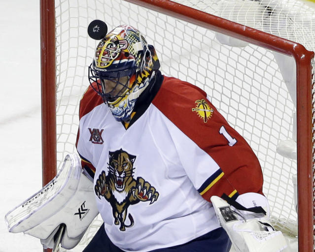 Florida Panthers goalie Roberto Luongo stops a shot with his helmet during the third period of an NHL hockey game against the San Jose Sharks on Tuesday, March 18, 2014, in San Jose, Calif. Florida won 3-2. (AP Photo/Marcio Jose Sanchez)