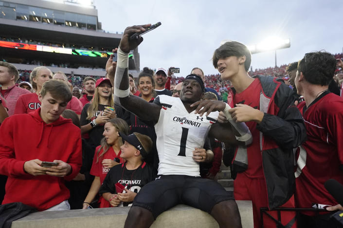 Cincinnati's Ahmad Gardner (1) takes a selfie as he celebrates with fans after Cincinnati defeated Notre Dame, 24-13, in an NCAA college football game, Saturday, Oct. 2, 2021, in South Bend, Ind. (AP Photo/Darron Cummings)