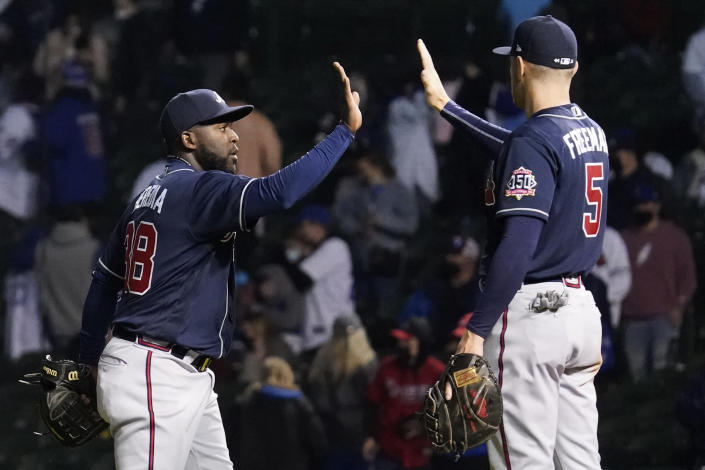 Atlanta Braves' Guillermo Heredia, left, celebrates with Freddie Freeman after they defeated the Chicago Cubs in a baseball game in Chicago, Sunday, April 18, 2021. (AP Photo/Nam Y. Huh)