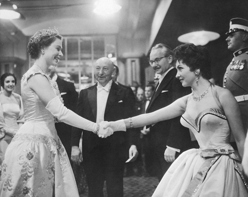 <p>Dressed in a satin gown with a sweetheart neckline and a diamond choker, Gina Lollobrigida looked positively royal when she met Queen Elizabeth in 1955. The monarch's outfit still wins though, as it included a sparkling tiara. </p>