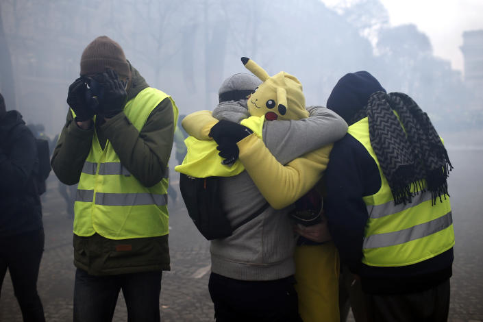 Demonstrators wearing yellow vests protect their eyes amid tear gas on the Champs-Elysees avenue Saturday, Dec. 8, 2018 in Paris. (Photo: Rafael Yaghobzadeh/AP)