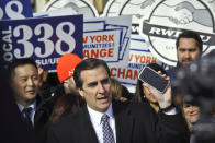 FILE - This Nov. 14, 2018 file photo shows New York State Sen. Michael Gianaris, center, as he calls on supporters to remove the Amazon app from their phones and boycott the company, as he address a coalition rally and press conference, in New York. Big tech's outsized influence over society has become one of the biggest battlefronts in state legislatures this year. Lawmakers are taking on tech and social media companies over a wide range of issues, including anti-trust, digital privacy, taxing ad sales, net neutrality and censorship. (AP Photo/Bebeto Matthews, File)