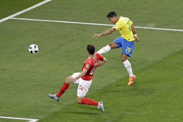 Brazil's Roberto Firmino, right, makes an attempt to score as Switzerland's Fabian Schaer tries to stop him during the group E match between Brazil and Switzerland at the 2018 soccer World Cup in the Rostov Arena in Rostov-on-Don, Russia, Sunday, June 17, 2018. (AP Photo/Andrew Medichini)
