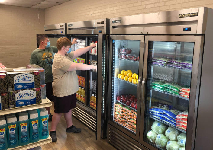 In this provided by Anthony Love, Hunter Weertman, 16, left, works alongside a fellow student to stock the refrigerator in the student-led free grocery store at Linda Tutt High School on Nov. 20, 2020, in Sanger, Texas. The store provides food, toiletries and household items to students, faculty and community members in need. (Anthony Love via AP)