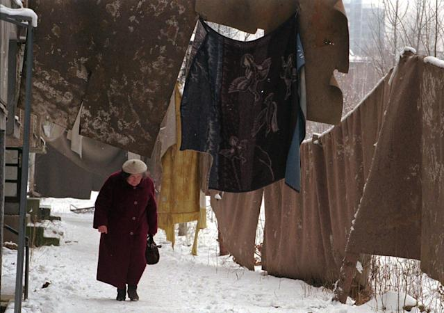 <p>A Bosnian Serb woman passes under blankets hung as an anti-sniper screen on Jan. 22, 1996, in the Sarajevo suburb of Grbavica. (Photo: Jacqueline Larma/AP) </p>