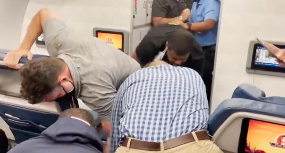 Passengers and flight attendants subduing an unruly man who forced a plane to be diverted after reportedly trying to open a door mid-air.