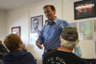 In this Sunday, Oct. 10, 2021, photo Republican Adam Laxalt, flanked by pictures of Presidents Abraham Lincoln and Ronald Reagan, talks to a supporter at the Douglas County Republican Party Headquarters on the final day of his Senate campaign's statewide tour in Gardnerville, Nev. Republican Laxalt hopes to win the race for Nevada's U.S. Senate seat by drawing stark between his positions and the direction he says Democrats and their allies in Big Tech, Hollywood and the media are taking the country. (AP Photo/Sam Metz)
