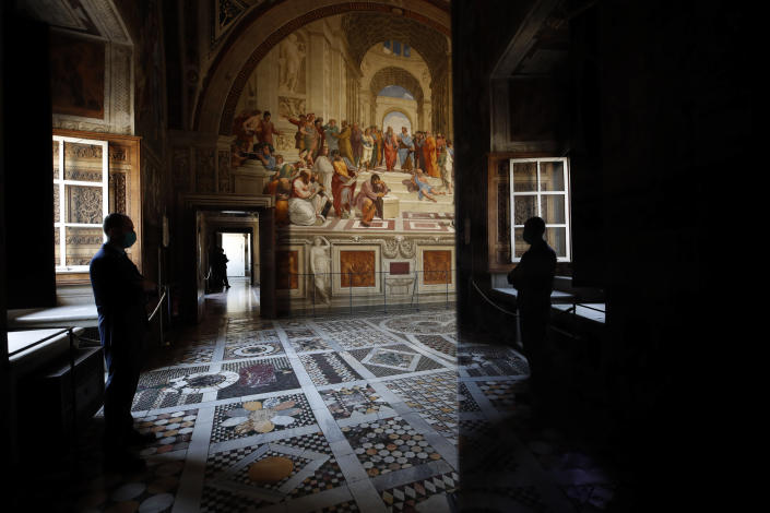 An employee wearing a mask to prevent the spread of COVID-19 stands inside a Raphael Room of the Vatican Museums on their reopening, in Rome, Monday, May 3, 2021. The Vatican Museums reopened Monday to visitors after a shutdown following COVID-19 containment measures. (AP Photo/Alessandra Tarantino)