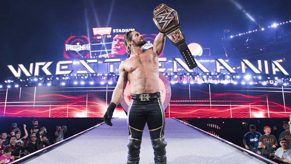 WWE Wrestler Seth Rollins holds up a title belt.