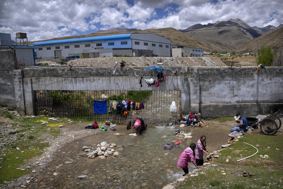 Women wash clothes in a stream near an industrial area in a village outside of Lhasa in western China's Tibet Autonomous Region, as seen during a rare government-led tour of the region for foreign journalists, Wednesday, June 2, 2021. Long defined by its Buddhist culture, Tibet is facing a push for assimilation and political orthodoxy under China's ruling Communist Party. (AP Photo/Mark Schiefelbein)