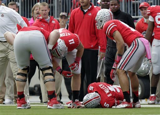 Ohio State quarterback Braxton Miller lies injured on the ground after being tackled by a Purdue player during the third quarter of an NCAA college football game on Saturday, Oct. 20, 2012, in Columbus, Ohio. Ohio State defeated Purdue 29-22 in overtime. (AP Photo/Jay LaPrete)