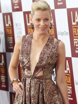 """The """"Hunger Games"""" actress in a very daring metallic copper style cut-out plunge dress at the LAFF premiere of 'People Like Us'"""