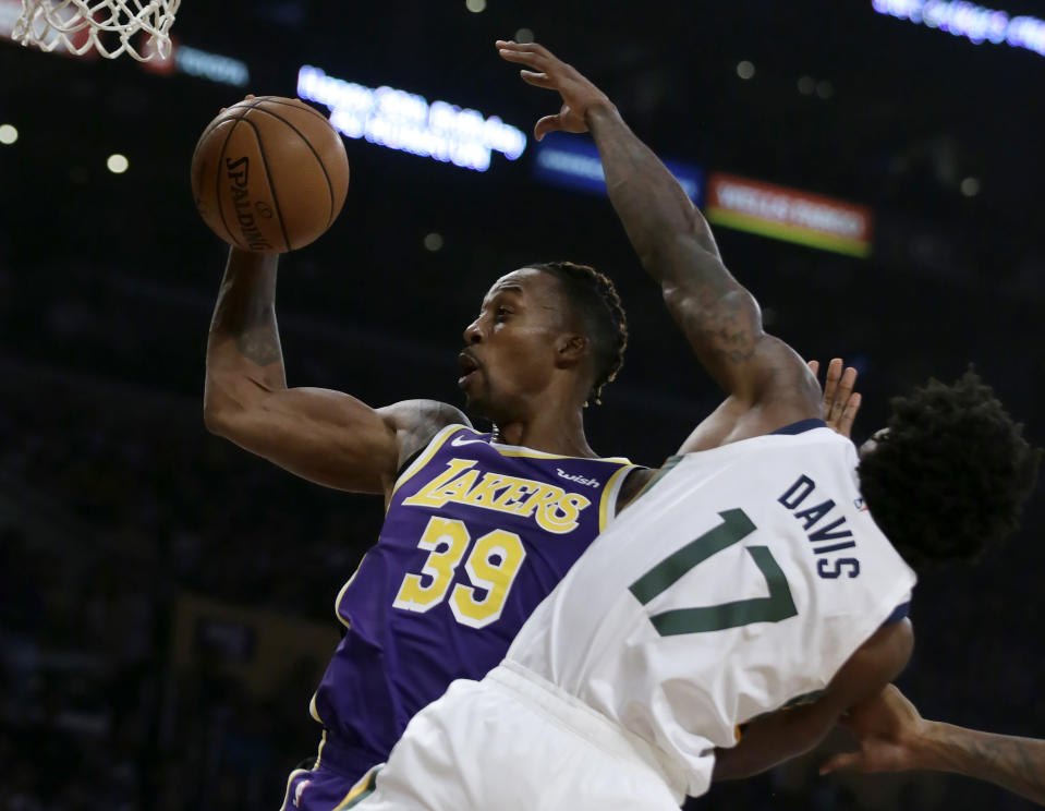 Los Angeles Lakers center Dwight Howard, left, rebounds the ball next to Utah Jazz center Ed Davis during the first half of an NBA basketball game in Los Angeles, Friday, Oct. 25, 2019. (AP Photo/Alex Gallardo)