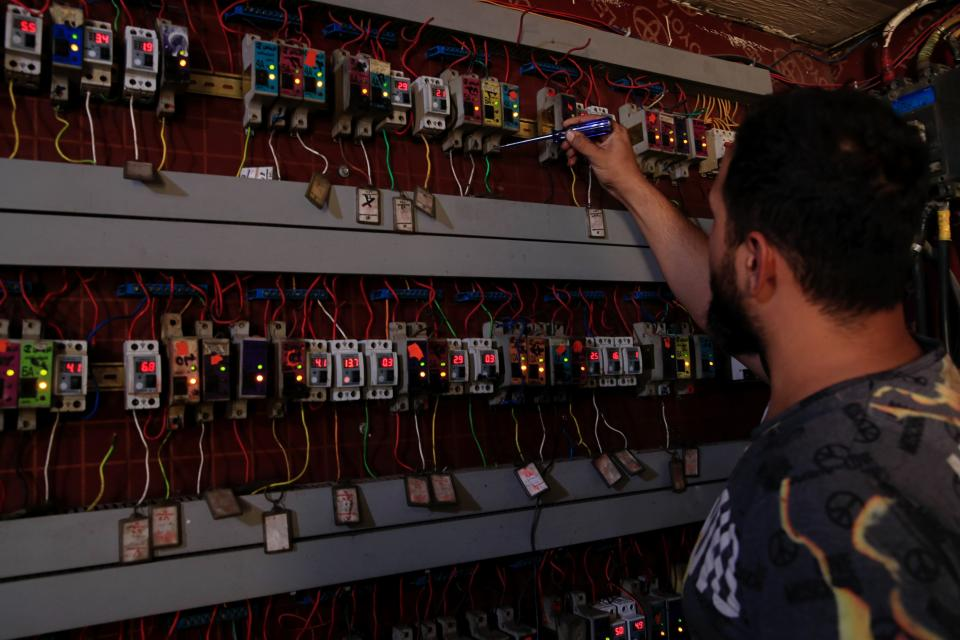 Muqtada Haider turns the switches to transfer electricity to private homes in Baghdad, Iraq, Friday, Sept. 10, 2021. In Iraq, electricity is a potent symbol of endemic corruption, rooted in the country's sectarian power-sharing system. This contributes to chronic electrical outages of up to 14 hours a day in a major oil-producing nation with plentiful energy resources. (AP Photo/Hadi Mizban)