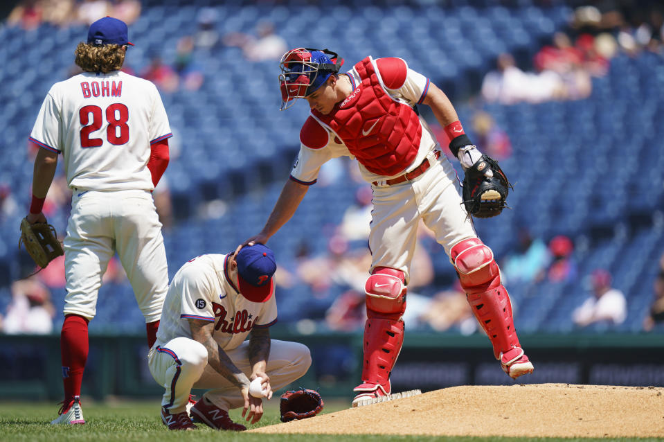 Philadelphia Phillies catcher J.T. Realmuto, right, comes over to talk with starting pitcher Vince Velasquez, center, after Velasquez hit Washington Nationals' Austin Voth in the face with a pitch during the third inning of a baseball game, Sunday, June 6, 2021, in Philadelphia. (AP Photo/Chris Szagola)