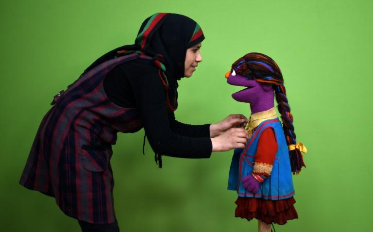 """Zari (R) was the first female Afghan muppet on """"Sesame Street"""" (known as """"Baghch-e-Simsim"""") and her message was girl power -- she is seen here in 2016 with Raziya Nazari at a Kabul studio (AFP Photo/WAKIL KOHSAR)"""