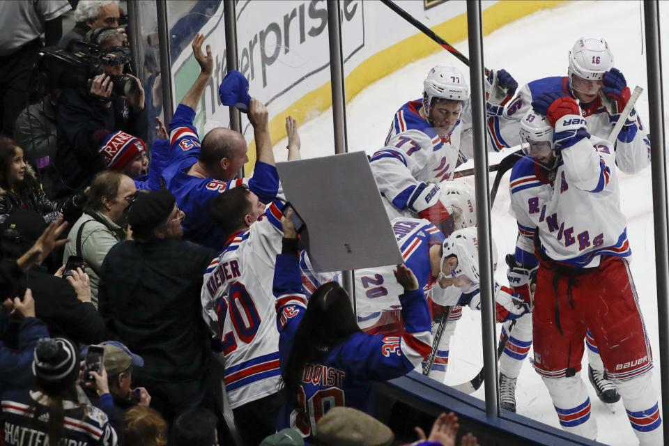 Fans watch as New York Rangers' Chris Kreider (20) celebrates with teammates after scoring a goal during the third period of an NHL hockey game against the New York Islanders Thursday, Jan. 16, 2020, in Uniondale, N.Y. The Rangers won 3-2. (AP Photo/Frank Franklin II)