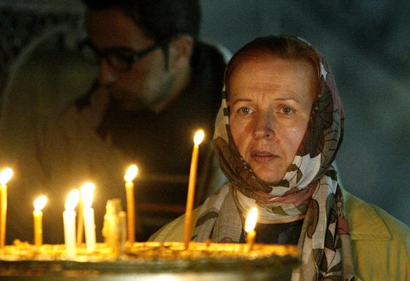 A Catholic pilgrim looks at lit candles outside of the Grotto at the Church of Nativity, traditionally believed by Christians to be the birthplace of Jesus Christ, in the West Bank town of Bethlehem, Monday, Dec. 24, 2012. Thousands of Christian worshippers and tourists arrived in Bethlehem on Monday to mark Christmas at the site where many believe Jesus Christ was born. (AP Photo/Adel Hana)