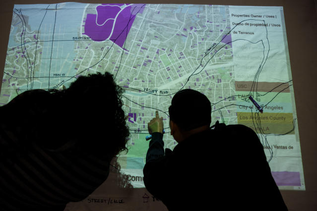 Attendees draw a community power map on a projection showing where property sales, speculation, rent increases and plans for a Biotech corridor are during an East Side Leads event at the Wellness Center in Boyle Heights, Los Angeles, in February. (Photo: Patrick T. Fallon for Yahoo News)