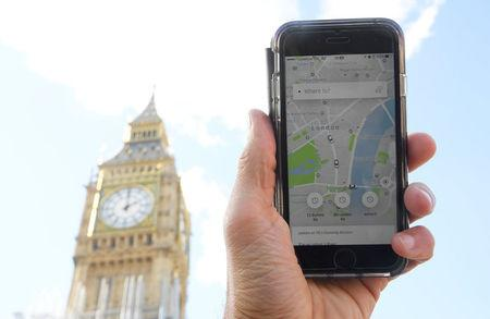 A photo illustration shows the Uber app on a mobile telephone, as it is held up for a posed photograph in central London