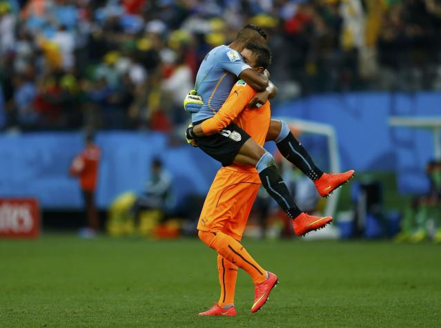 Uruguay's Jose Maria Gimenez (top) hugs teammate Fernando Muslera after Luis Suarez (unseen) scored against England during their 2014 World Cup Group D soccer match at the Corinthians arena in Sao Paulo June 19, 2014. REUTERS/Ivan Alvarado (BRAZIL - Tags: SPORT SOCCER WORLD CUP TPX IMAGES OF THE DAY)