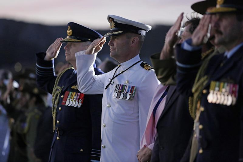 Chief of Defence Force Air Chief Marshall Mark Binskin, AC and Commanding Officer HMNZS Te Kaha, Commander Dave McEwan, RNZN, salute during the national anthems of Australia and New Zealand, in Albany, Western Australia, on October 31, 2014 (AFP Photo/Lsis Jayson Tufrey)