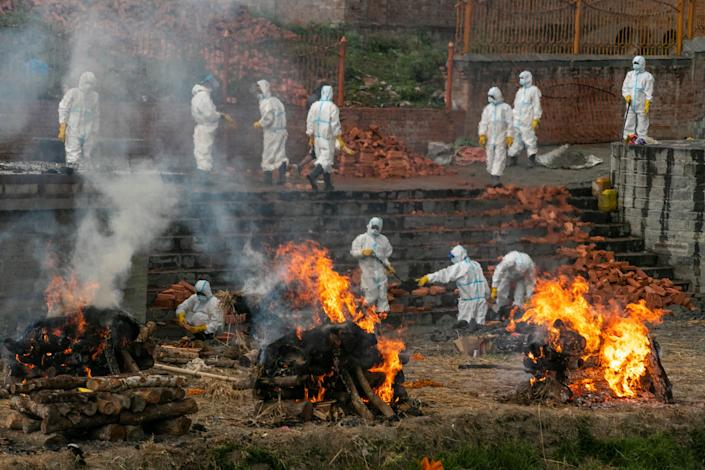 <p>File image:  In this 5 May, 2021 photo, Nepalese men in personal protective suits cremate the bodies of Covid-19 victims while others extend the crematorium as the number of deaths rise near Pashupatinath temple in Kathmandu, Nepal</p> (AP)