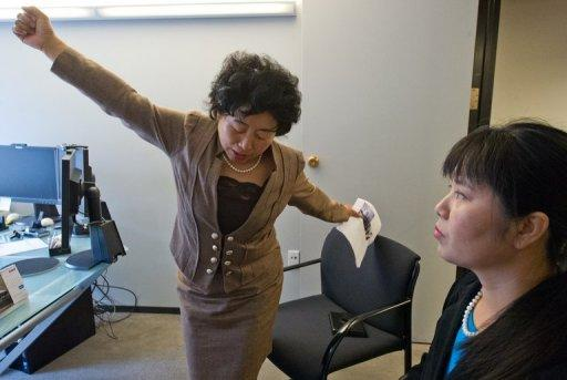 Former China labor camp detainee, Wang Chunying (L), demonstrates a position she was forced to take while handcuffed between two beds as her compatriot Ma Chunmei looks on during an interview at the AFP offices in Washington, DC, on April 30, 2013