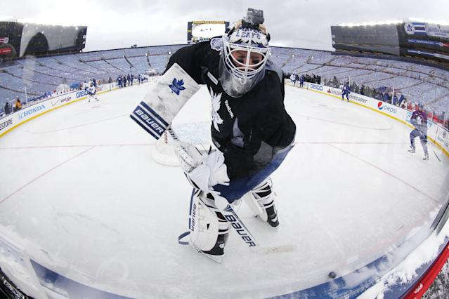 Toronto Maple Leafs goalie James Reimer clears a puck during practice on the outdoor rink for the NHL Winter Classic hockey game against the Detroit Red Wings at Michigan Stadium in Ann Arbor, Mich., Tuesday, Dec. 31, 2013. The game is scheduled for New Year's Day. (AP Photo/Paul Sancya)