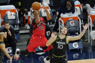 Toronto Raptors' Norman Powell (24) shoots as he is fouled by Minnesota Timberwolves' Jake Layman (10) during the second half of an NBA basketball game Friday, Feb. 19, 2021, in Minneapolis. (AP Photo/Jim Mone)