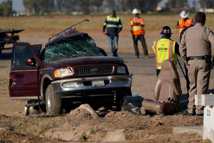 Law enforcement officers sort evidence and debris at the scene of a deadly crash in Holtville, Calif., on March 2. Authorities say a semitruck crashed into an SUV carrying 25 people on a Southern California highway, killing at least 13 people.
