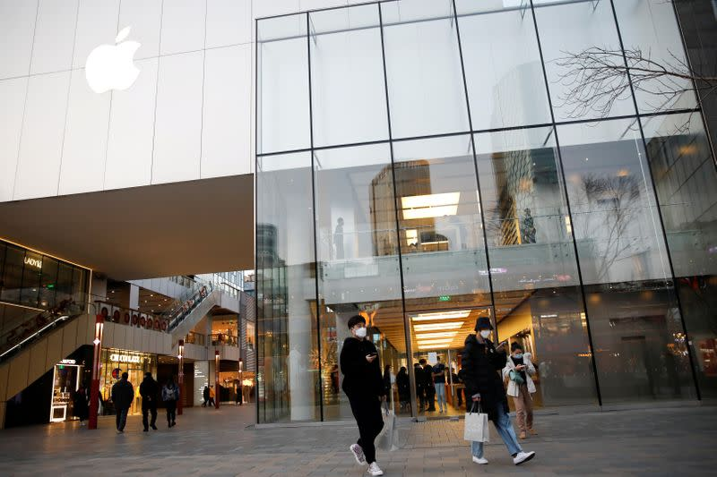 FILE PHOTO: People wearing face masks walk in front of an Apple store at a shopping mall, as the country is hit by an outbreak of the new coronavirus, in Beijing