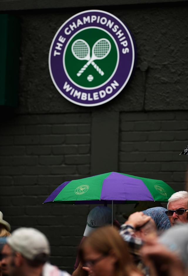 LONDON, ENGLAND - JUNE 27: A spectator shelters under an umbrella as rain interrupts play during the Ladies' Singles second round match between Agnieszka Radwanska of Poland and Mathilde Johansson of France on day four of the Wimbledon Lawn Tennis Championships at the All England Lawn Tennis and Croquet Club on June 27, 2013 in London, England. (Photo by Dennis Grombkowski/Getty Images)