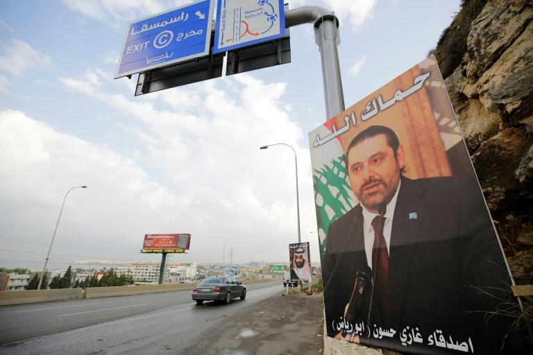 """A poster of Lebanese prime minister Saad Hariri, who resigned last week in a televised speech from Riyadh, hangs on the side of a road in the Lebanese city of Tripoli with a depiction in Arabic that reads """"God protect you"""""""